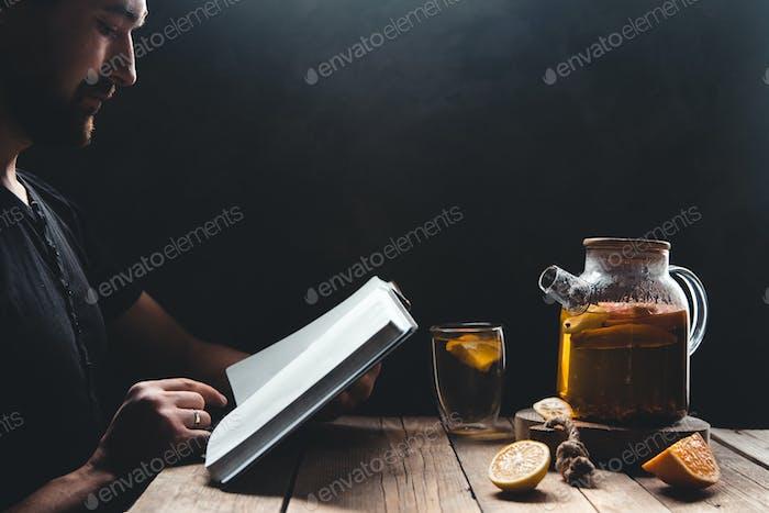 Ein Mann, der ein Buch mit Zitrustee liest. Bildung, gesundes Getränk, Ausbildung