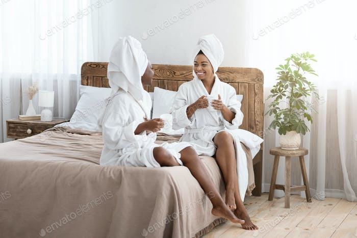 Pretty african american girlfriends in bathrobes drinking coffee