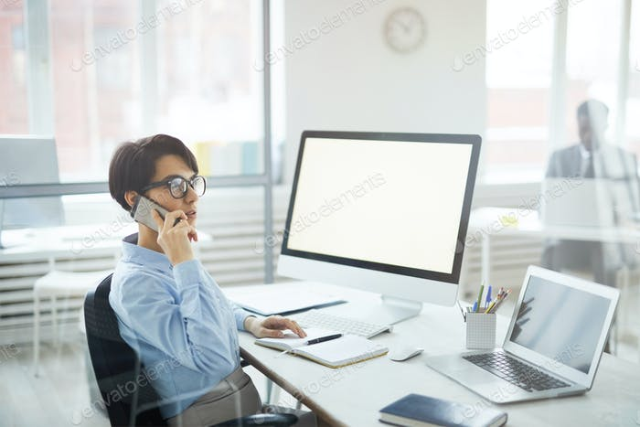 Businesswoman Speaking by Phone at Workplace