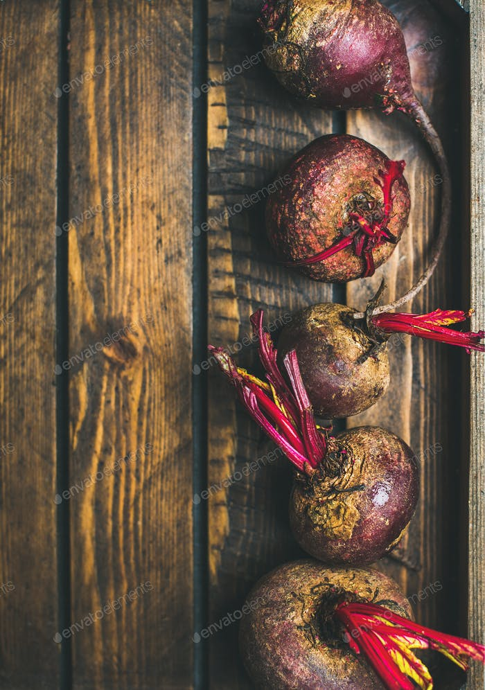 Raw organic purple beetroots in rustic wooden box, copy space