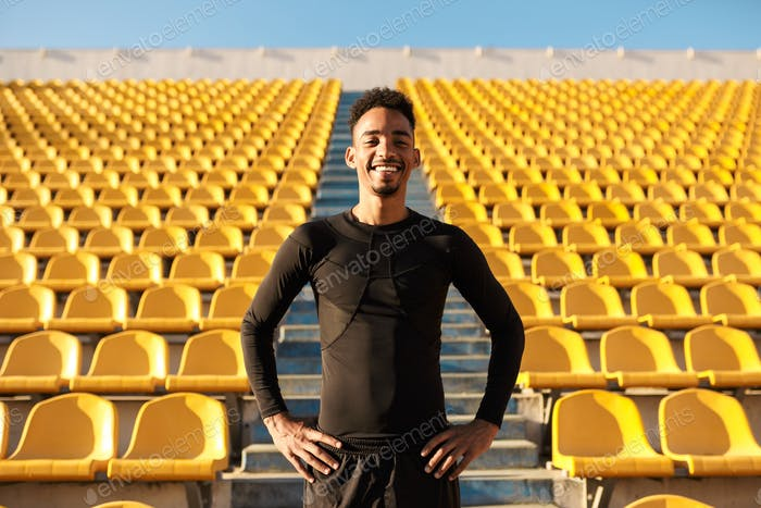 Young joyful African American sportsman happily looking in camera among empty stadium seats