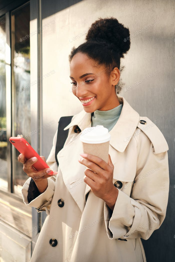Smiling African American girl in stylish trench coat with coffee happily using cellphone outdoor