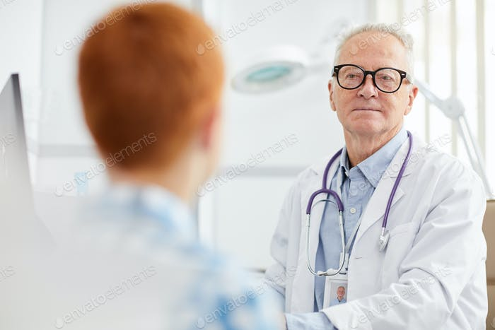 White-Haired Senior Doctor with Little Patient