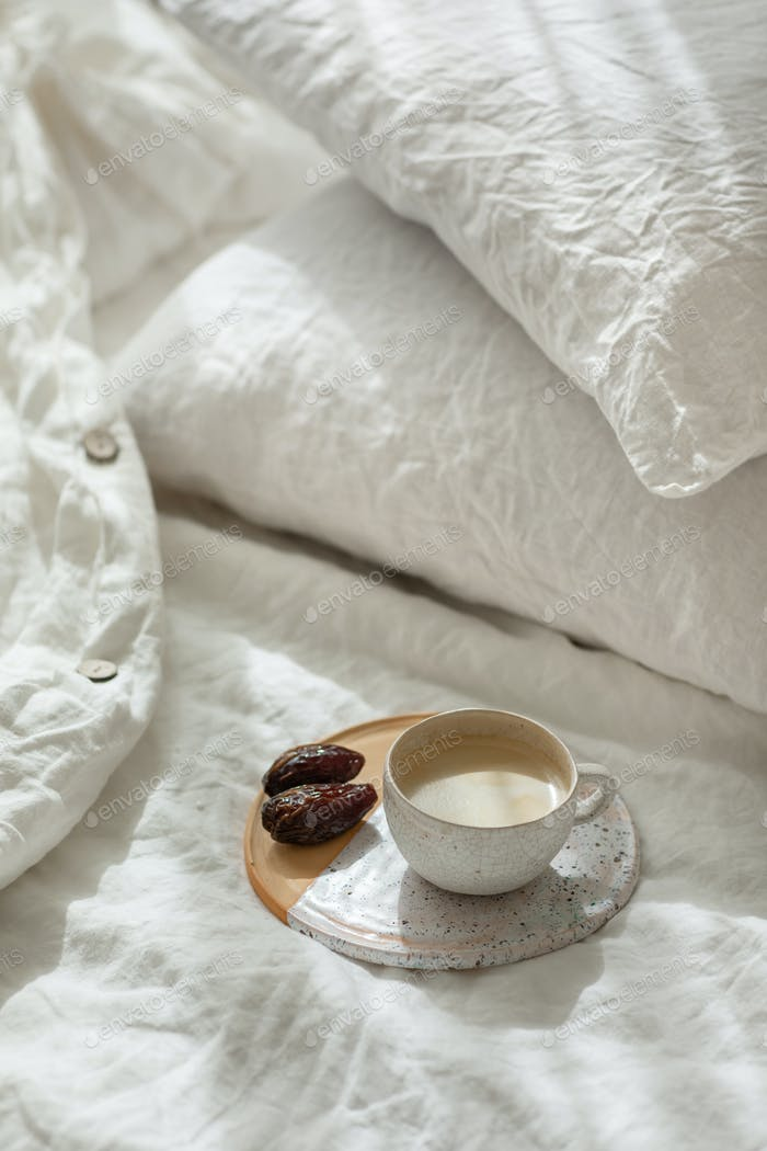 Cup of fresh coffee bed on ceramic tray, morning mood. Linen cotton textile bedclothes with wrinkle