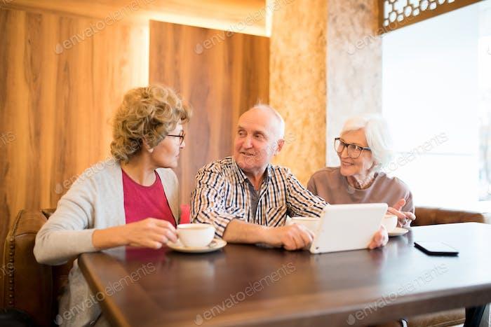 Handsome man talking to elderly ladies