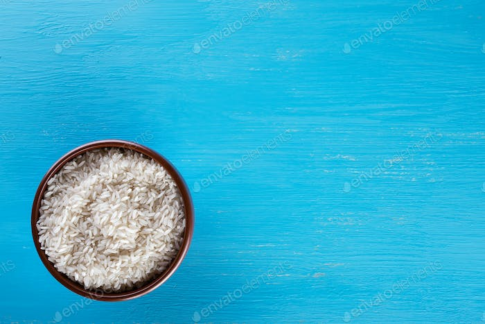 Clay brown plate with raw rice on blue background