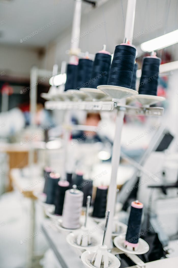 Black threads on spools closeup, overlock machine
