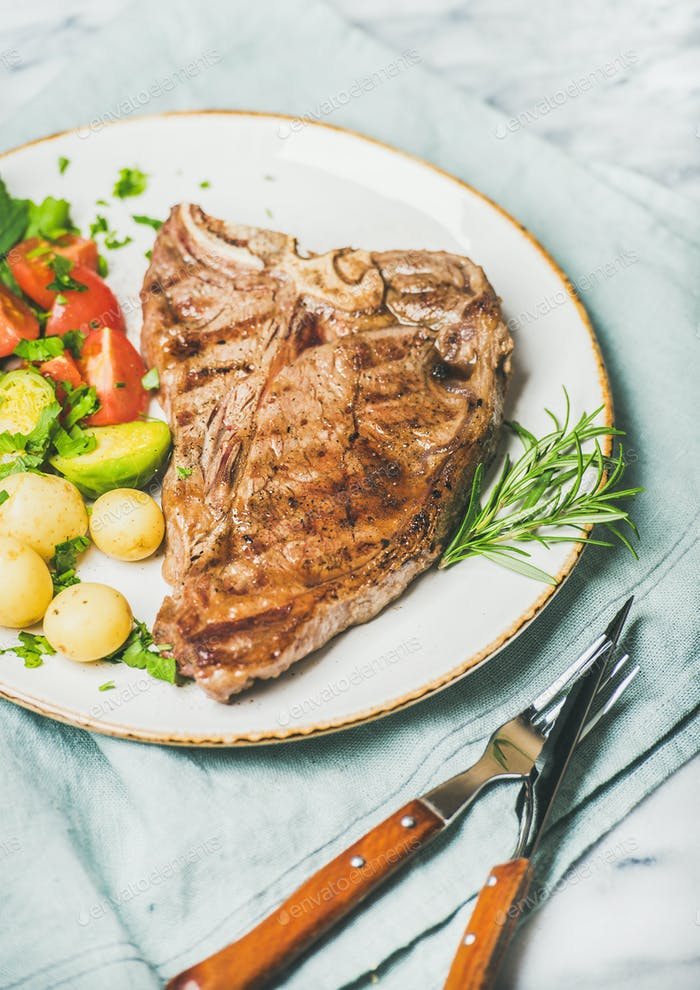 Cooked beef tbone steak with vegetables and fresh rosemary