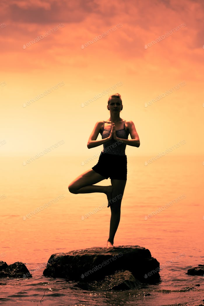 Young Woman doing the Tree Yoga Position During Sunset