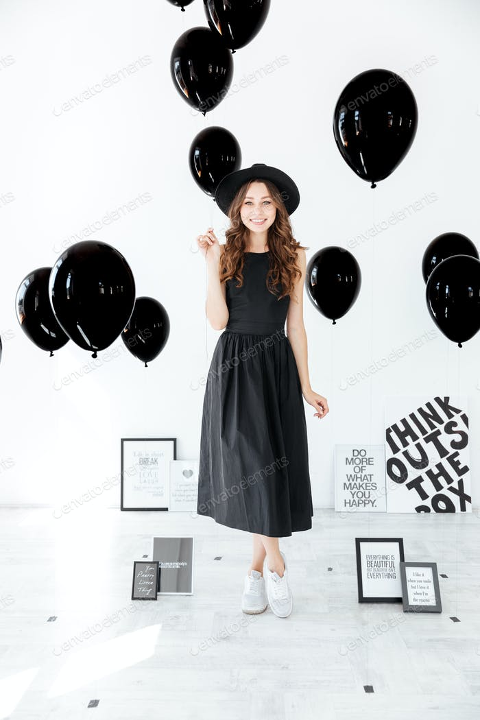 Full length of cheerful woman standing and holding black balloons