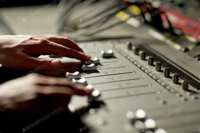 Hände auf Mischpult im Musikaufnahmestudio