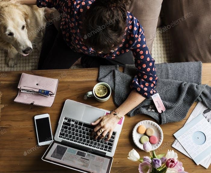 Женщина с помощью ноутбука покупки онлайн и домашних собак
