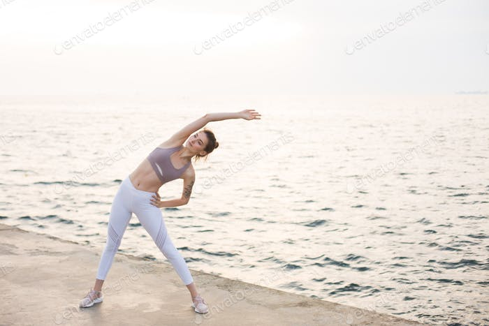 Young lady in sporty top and leggings practicing yoga with amazi