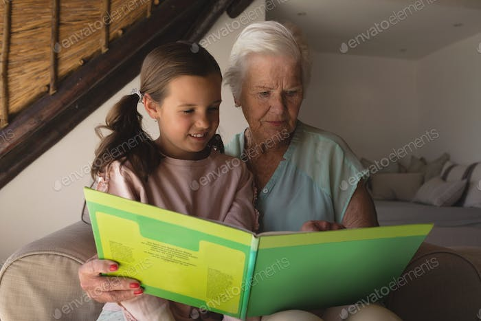 Front view of a grandmother and granddaughter reading story book in living room at home