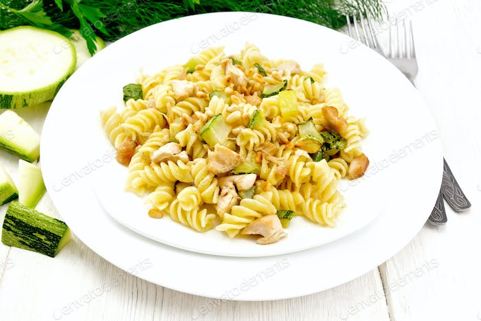 Fusilli with chicken and zucchini in two plates on light board