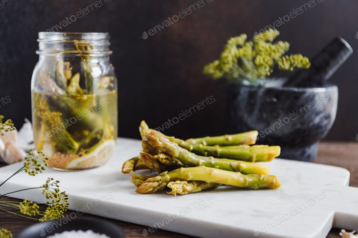 Pickled asparagus on a white marble tray