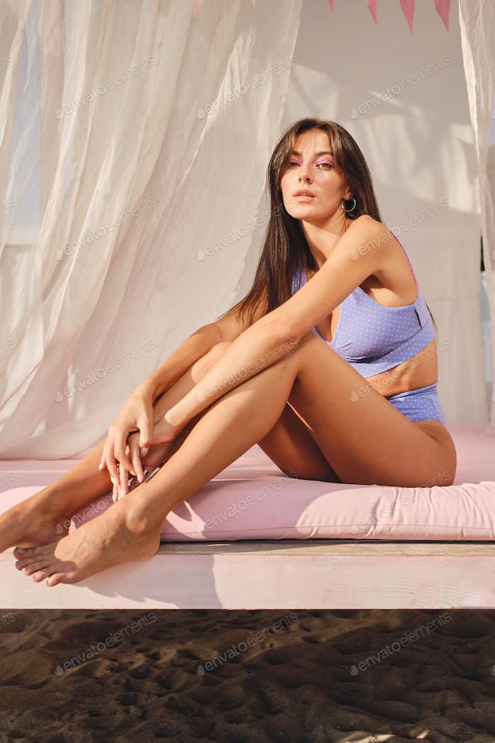 Gorgeous brunette girl in cute swimsuit sensually looking in camera on beach bed with curtains