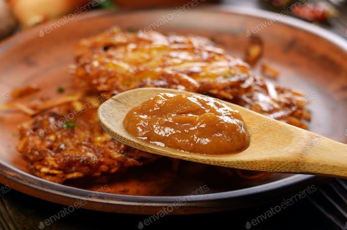 Applesauce in front of fresh homemade tasty potato pancakes in c