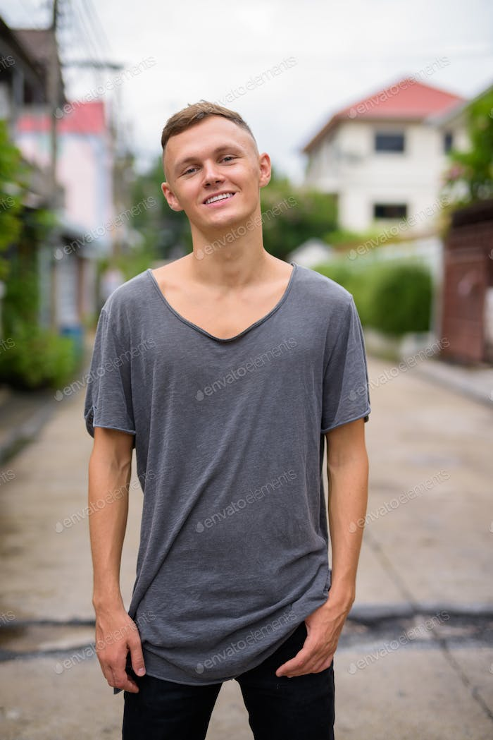 Young man wearing gray shirt in the streets outdoors