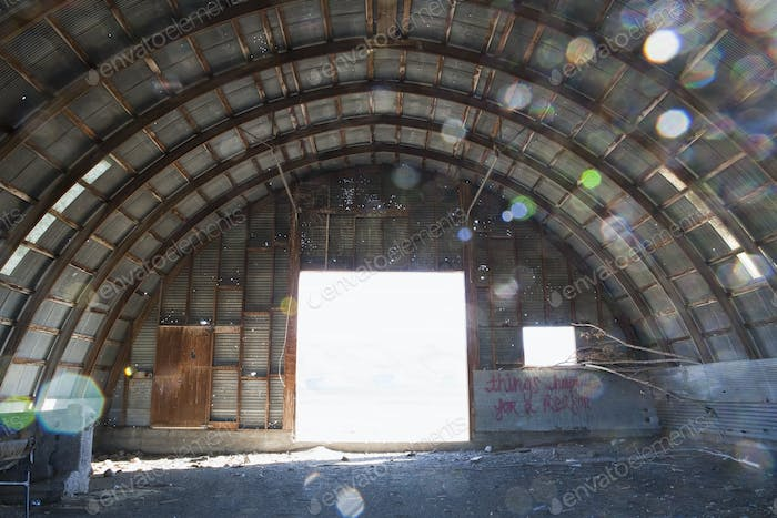 Interior of a deserted building, big open door and arched roof