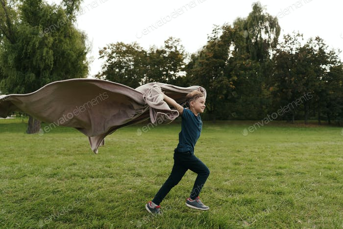 Cheerful boy running with a flying blanket in the park