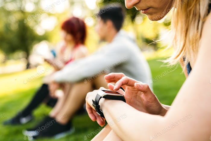 Unrecognizable athlete in park setting her smartwatch.