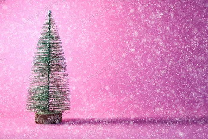 christmas tree on pink background with snow