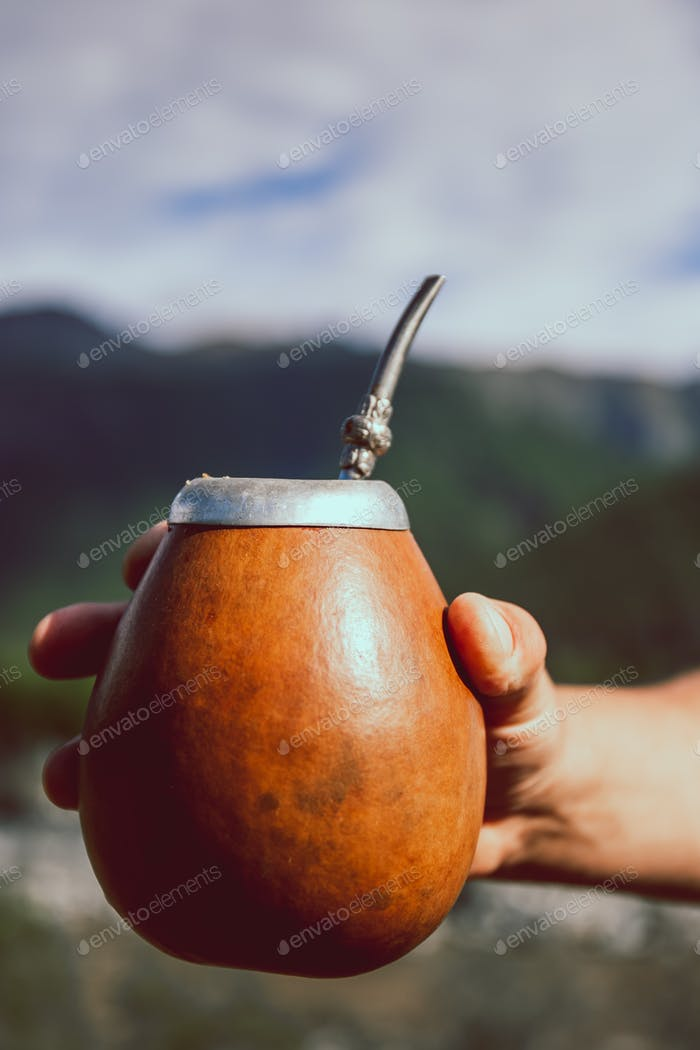 Man holding calabash yerba mate in nature. Travel and adventure concept