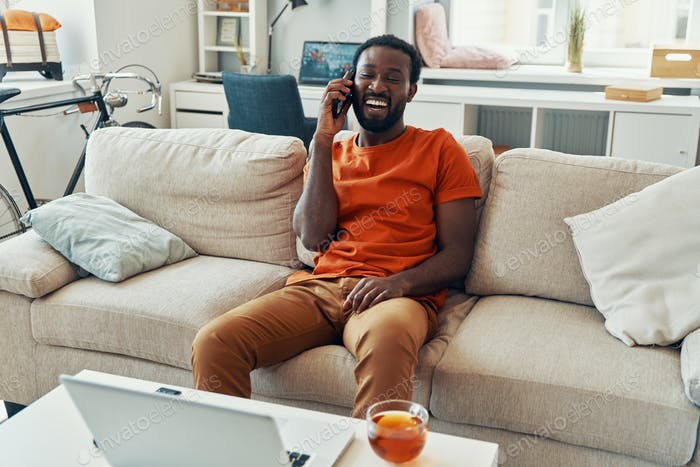 Carefree young African man talking on the phone and smiling while spending time at home