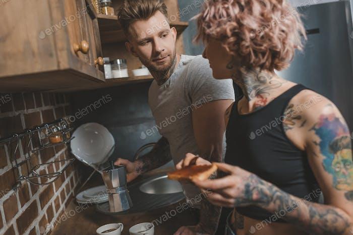 Tattooed Couple Cooking Breakfast at Kitchen