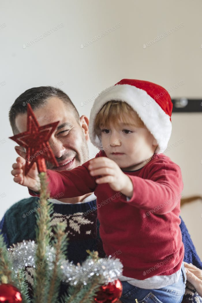 happy family with a young child decorating a christmas tree at h