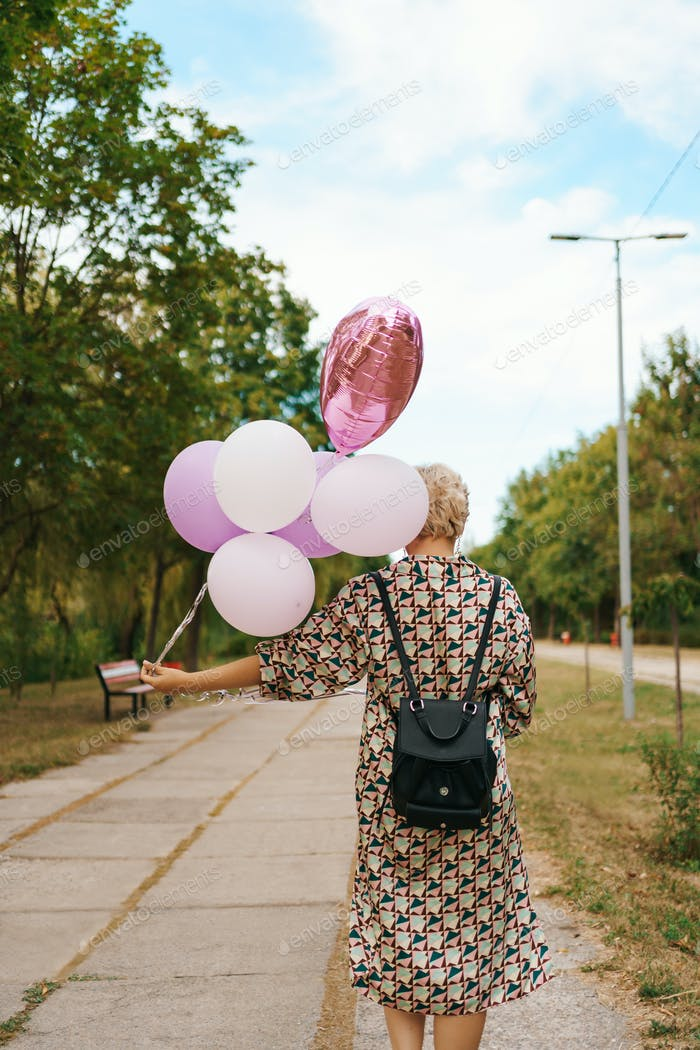 Blonde woman with pink balloons