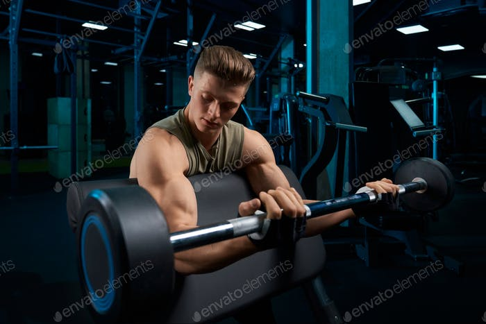 Bodybuilder training biceps with barbell