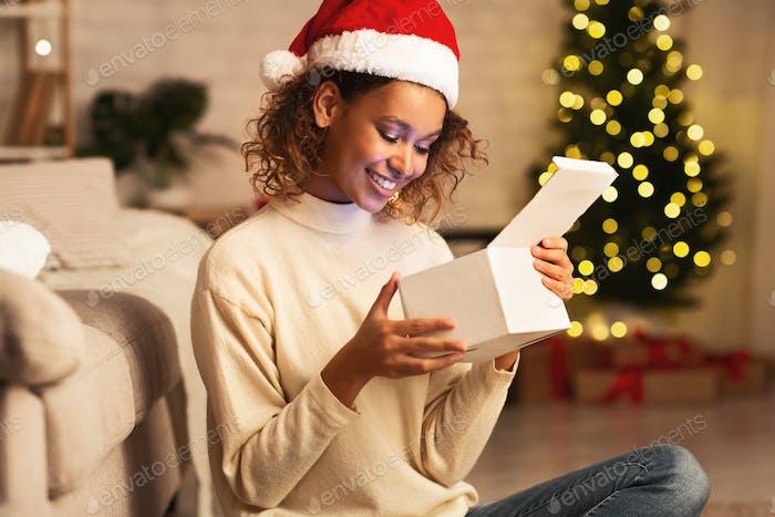 Afroamerikanisches Mädchen im Inneren Weihnachtsgeschenk zu Hause