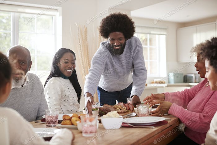 Middle aged black man bringing roast meat to the table for the Sunday family dinner