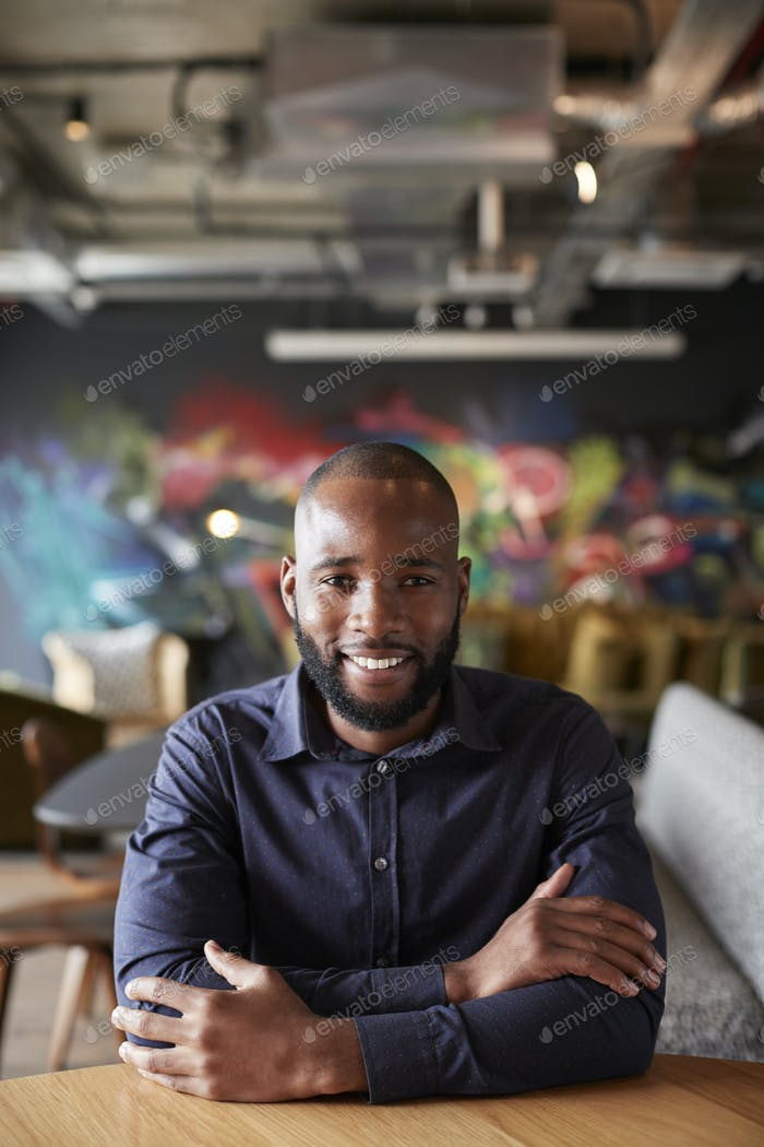 Mid adult black male creative sitting at a table with arms crossed smiling to camera, close up