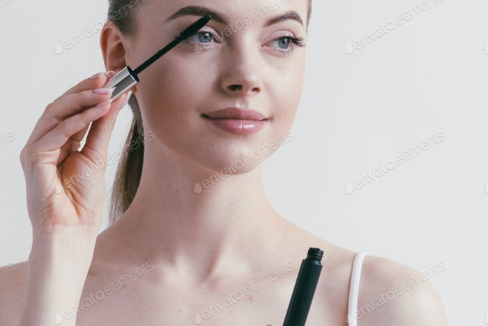 Mascara woman portrait, beautiful brunette model applying brush mascars eyes lashes