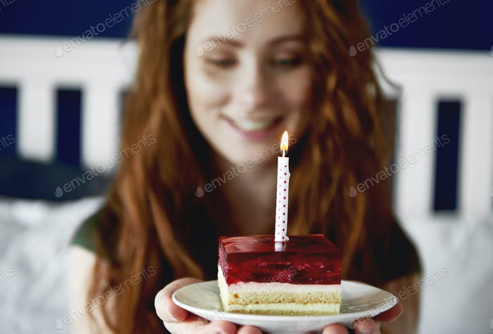 Close up of woman with a piece of birthday cake