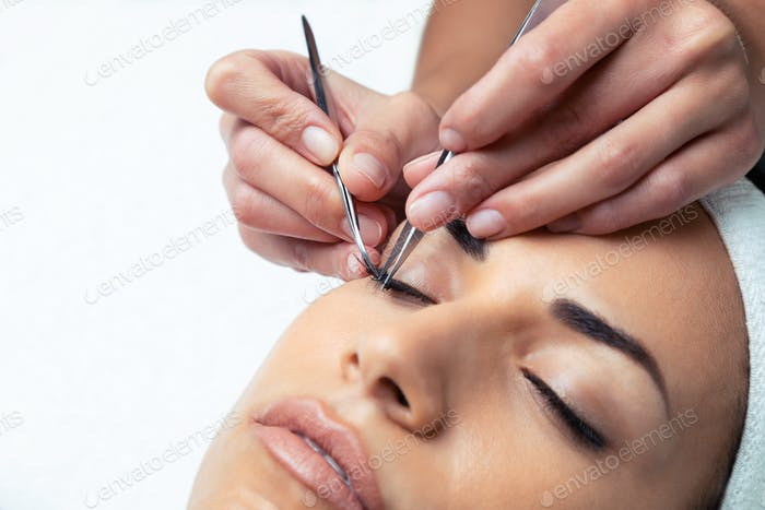 Cosmetologist doing the eyelash extension procedure on a woman over white background.
