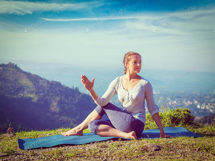 Woman doing Ardha matsyendrasana asana outdoors
