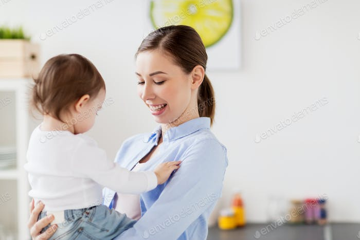 happy mother and little baby girl at home kitchen