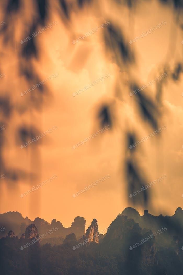 Orange sky above rocky karst mountains in Zhangjiajie