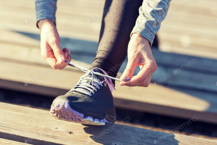 close up of sporty woman tying shoelaces outdoors