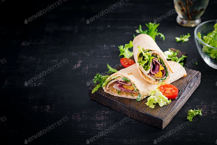 Fresh tortilla wraps with ham beef and fresh vegetables on wooden board.