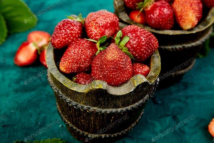 Erdbeere in der Schüssel auf einem grünen Hintergrund.