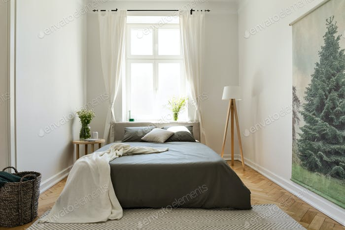 Blanket on dark bed in bright bedroom interior with flowers, lam