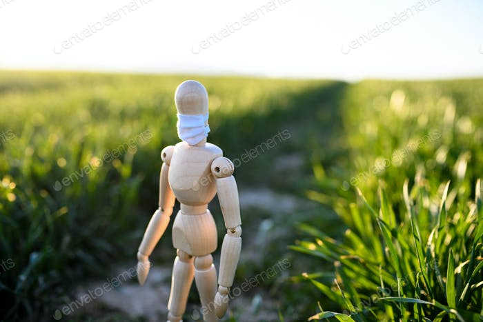 Wooden mannequin with face mask in nature, corona virus and lockdown concept
