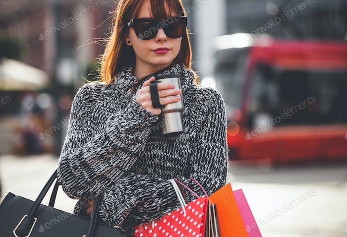 Женщина гуляет по улице с кофейной чашкой и сумками для покупок, концепция городской жизни