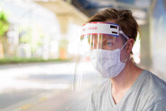 Young man with mask and face shield at the bus stop for protection from corona virus outbreak