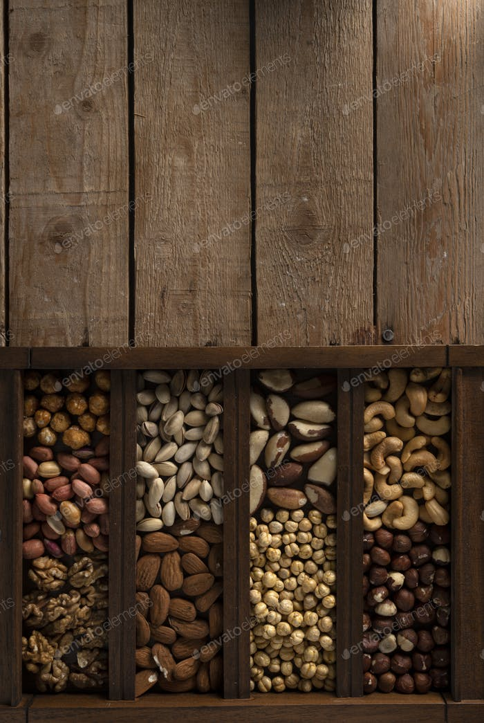 Mix of nuts in a wooden box on a wooden surface